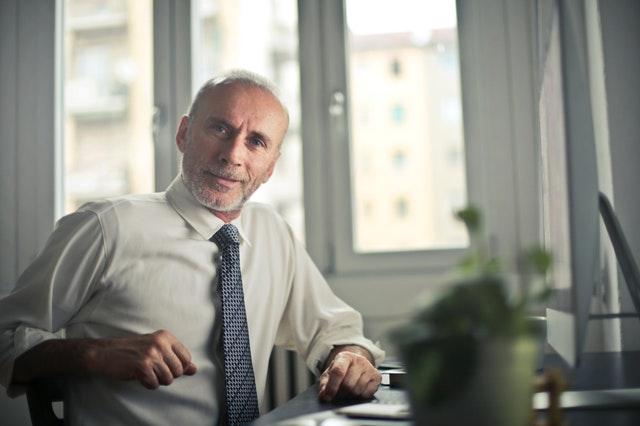 Starší usmiaty muž v bielej košeli sedí v kancelárii