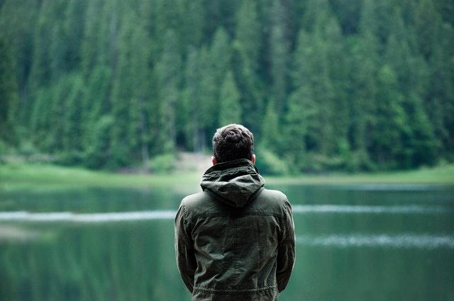Muž v zelenej bunde stojí pred jazerom vedľa lesa