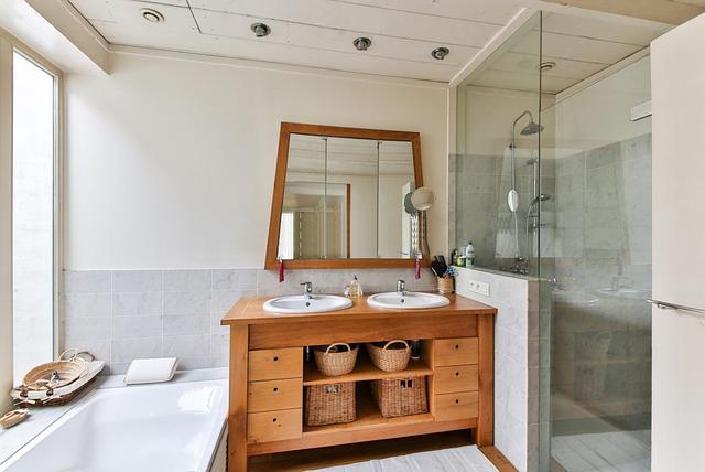 Priestranná kúpeľňa s dreveným nábytkom a preskleným sprchovacím kútom.jpg