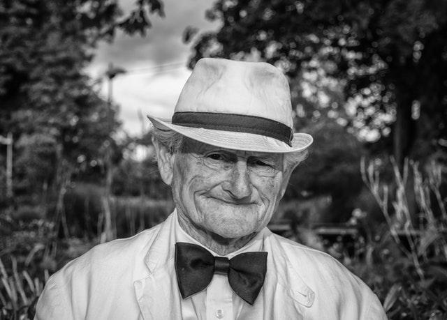 Starý pán v klobúku a s motýlikom sa usmieva.jpg
