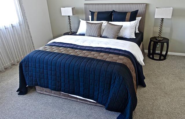 Čalúnená posteľ s s čalúneným čelom a s modrou dekou a vankúšmi.jpg