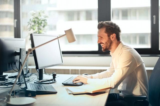 Muž sa smeje a pracuje na počítači