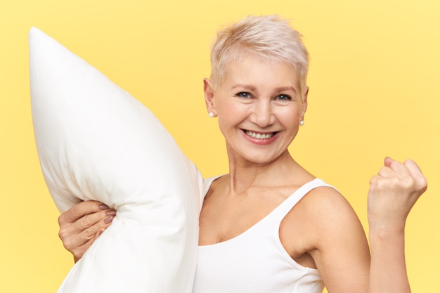 isolated-shot-joyful-excited-mature-european-female-clenching-fist-carrying-white-feather-pillow-feeling-full-energy-as-she-got-enough-sleep-looking-camera-with-radiant-vivacious-smile_343059-1996